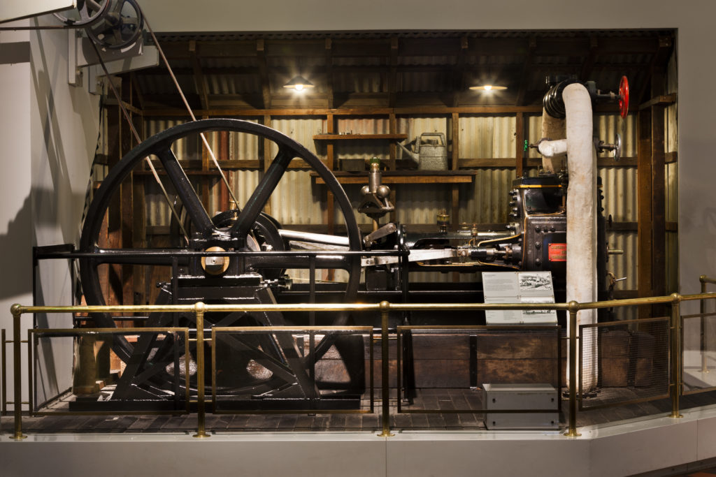 A Museum exhibit of a steam engine. It consists of a large flywheel attached to two pulleys. The engine sits on a large platform, bordered by a railing. Behind it is a mock engine shed wall with corrugated iron and an oil can sitting on a shelf.