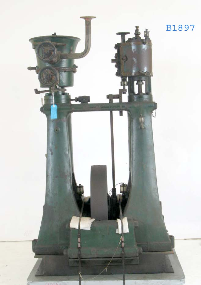 A museum artefact comprised of two painted metal towers. At their base and between the towers sits a wheel. At the top of each tower are various gears, knobs and levers.