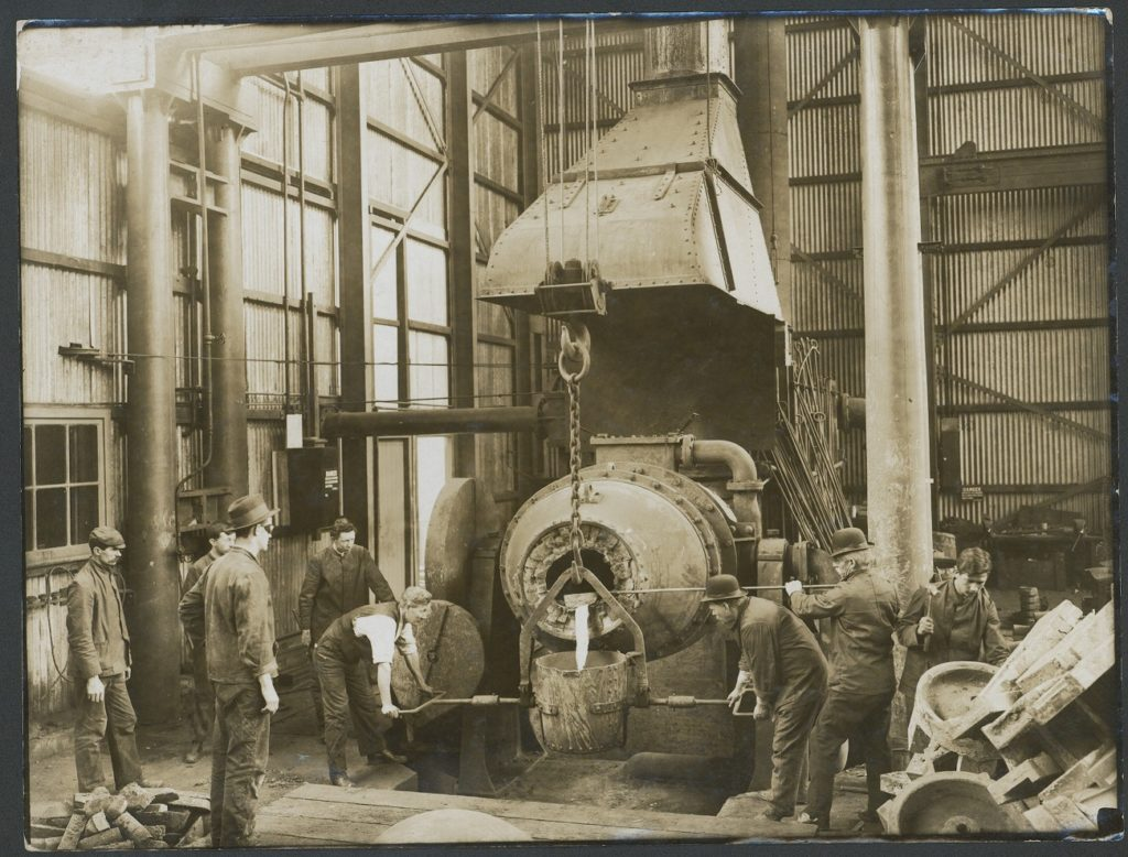 Sepia photograph of a factory scene. There is a large bucket hanging from a chain and pulley assembly, with two men holding the handles either side of the bucket. A third man guides molten metal into the bucket from a large furnace.