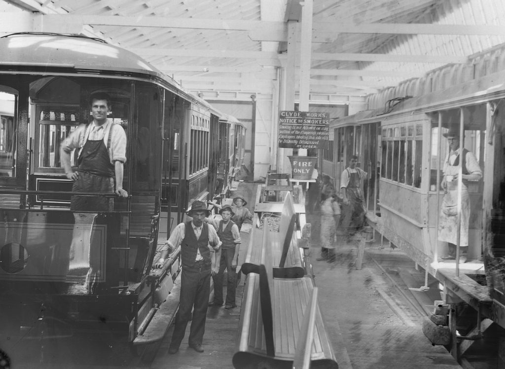 Black and white photograph of two trams parked inside a large carriage workshop surrounded by a group of men. Some are wearing work aprons with others in vests and trousers. A sign on a pole in the background reads 'CLYDE WORKS'.