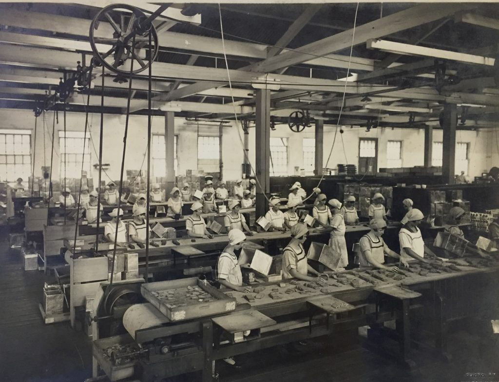 Black and white photograph of a group of female factory workers standing before four long conveyor belts packing biscuits into metal boxes. There are approximately ten women per conveyor belt.