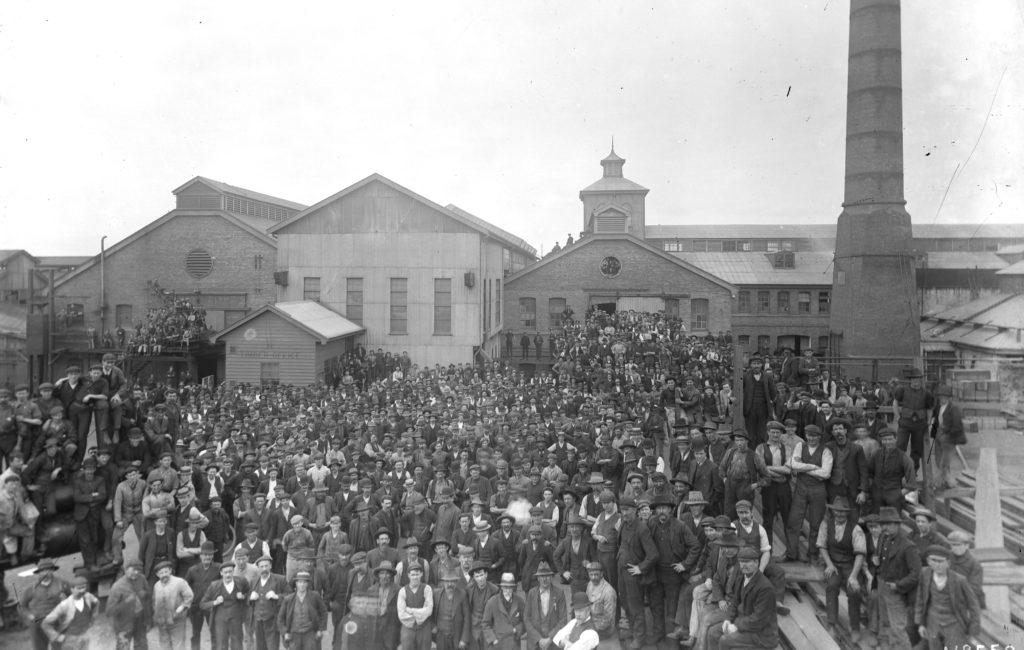 Black and white photograph of a crowd of men standing in front on a series of factory buildings. There is a large chimney on the right.