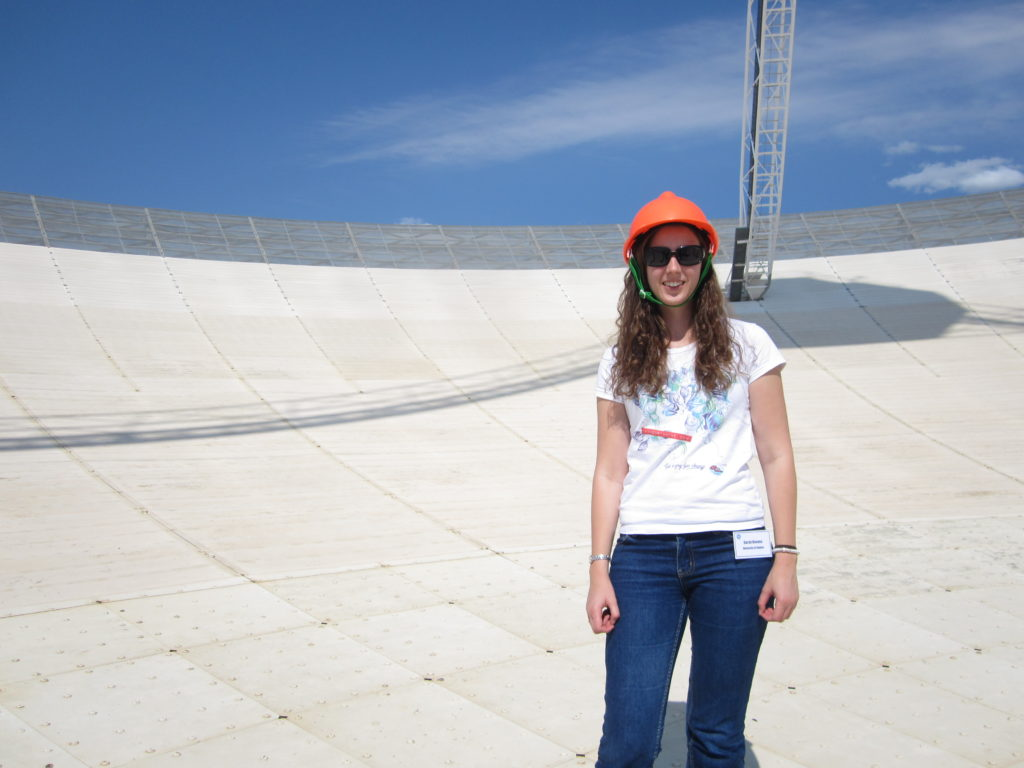 Photograph of Sarah Reeves on the surface of a large radio telescope dish.