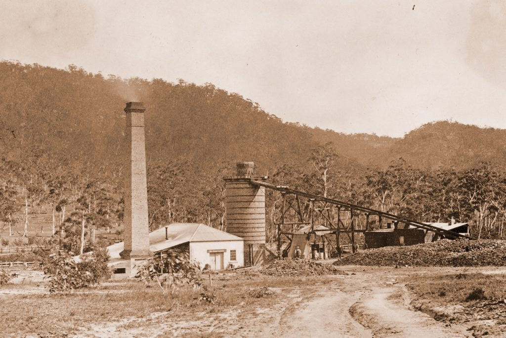 Sepia photograph showing a tall brick chimney attached to a small house and surrounded by Australian bushland. To the right is a large cylindrical brick structure (the furnace) connected to an inclining track.
