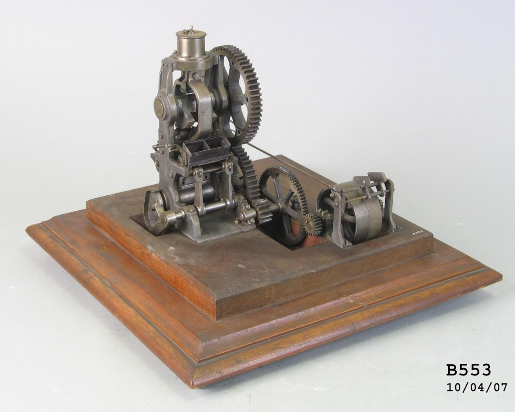 A model of a complex machine with four interlocking gears attached to a set of pistons and two brick shaped moulds. The working model is mounted on an ornate timber base.