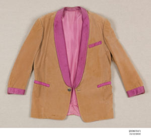 Velvet coat, fawn colour, with one silver button. Purple satin trim on lapels, collar, breast pocket, side pocket and cuffs. Satin lining very loosely stitched.