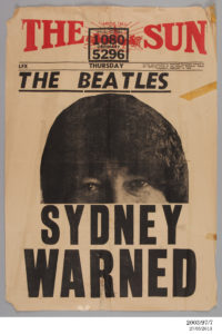 Poster advertising 'The Sun', a Sydney afternoon tabloid newspaper, dated Thursday 13 February 1964. Yellow paper with red masthead consisting of a horse chariot in front of a sunburst and the words 'The Sun'. Large photograph of the top half of John Lennon's face. The remaining text is in black, with the headline: 'The Beatles. Sydney warned'. The poster is torn in several places and has pieces of sticky tape attached.