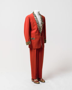 Mens suit consisting of jacket and trousers, worn by Johnny O'Keefe. -1 Jacket made of red fabric with black and cream coloured 'leopard print' velvet trimming at collar, cuffs and pockets. The jacket has a shawl collar with the collar and lapels lined with leopard print velvet which extends on the inside of the jacket to the waist. The jacket fastens at the waist with a single black plastic button which is sewn to the jacket with red cotton. The jacket is long sleeved and the cuffs are trimmed with leopard print velvet. The jacket has a fake external left breast pocket and two fake external waist pockets on the left and right sides, all pockets are trimmed with leopard print velvet. There are no internal pockets. The inside of the jacket is lined with a red [silk] fabric and leopard print velvet lines the collar and lapel area extending to the waist. The shoulders are slightly padded. The jacket has several moth holes including two on the back of the right shoulder and two below the button. The lining has a hole at the neck and is torn at each armhole and has detatched from the velvet below the buttonhole. The velvet lining is worn around the neck and above the button. -2 Trousers made of red fabric, matching trousers to jacket (98/32/2-1). Trousers have 2 side pockets and a coin pocket at the waist on the right side. Inside of pockets are made of a cream cotton fabric. Trousers are pleated at the waist at the front and back and have 4 wide belt loops formed in the pleats and one thin belt loop and the centre back of the waist which has a safety pin attached. Trousers fasten at the centre front with a metal zipper, a metal hook and eye and an internal button on the left side of the waist which fastens to a buttonhole on a triangular extension of red fabric on the right side. The trousers are unlined except for the inside waistband which is lined with a band of cream ribbed silk and the zipper which is lined with black [silk] fabric. The trousers are hemmed to give 