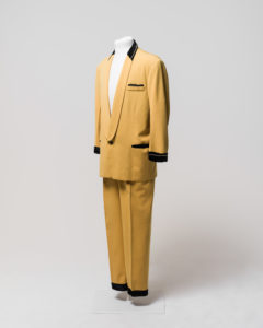 """Men's suit consisting of jacket and trousers, worn by Johnny O'Keefe. -1 Jacket made of yellow [cotton] fabric with black velvet trimming at collar, cuffs and pockets. The jacket has a shawl collar with the neck area trimmed with black velvet decorated with a string of diamantes around the neck. The lapels are of the same yellow fabric and extend to the single button fastening at the waist. The button is made of brownish-black plastic. The jacket is long sleeved and the cuffs are trimmed with black velvet decorated with a string of diamantes around the front half of both cuffs, some diamantes are missing from both cuffs. The jacket has a fake external left breast pocket trimmed with black velvet and diamantes, one diamante appears to be missing from the end of the string. The jacket also has two fake external waist pockets on the left and right sides which are trimmed with black velvet. The jacket is lined with salmon pink silk and has no internal pockets, the shoulders have some padding. A maker's label is sewn inside the jacket at the left breast, the label is cream coloured with black embroidered text """"Len Taylor/Sydney/American Clothes Stylist"""". The label is partly detached from the jacket. The jacket has black marks exteding horizontally from just above the right waist pocket and discolouration in the lining at the centre back neck area and in various places on the external yellow fabric. There are several moth holes in the lining and in the external fabric particularly just below the right waist pocket. -2 Trousers made of yellow [cotton] fabric, matching trousers to jacket (98/32/1-1). Trousers have 2 side pockets and are pleated at the front of waist. Trousers fasten at centre front with a metal zipper, metal hook and eye and internal button which fastens to button hole on a triangular extension of yellow fabric (this internal button is missing). There are seven belt loops around waist for a thin belt. Trousers are unlined except for the inside waist which i"""