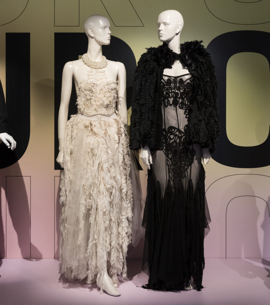 Two mannequins on display, one wearing white dress, the other wearing sheer black dress and cape.