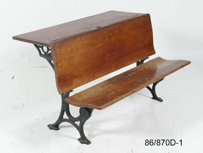 Dual seat wooden school desk with cast iron legs and pen rest and centre ink well on desktop.