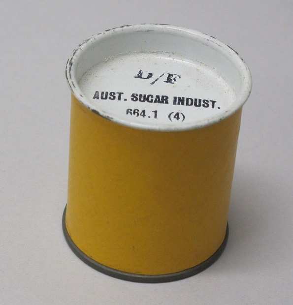 Metal cannister, cylindrical in shape, with a metal lid to store filmstrips.