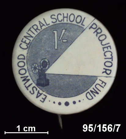 A round metal badge with a pin at the back to attached to clothing.