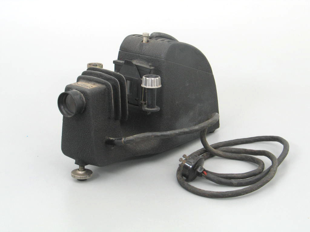 Projector unit, the body constructed in cast aluminium, painted black, with ventilation holes, containing an internal projection unit, an external revolving film transporting mechanism which sits within a niche in the body, a fixed focal length projection lens. The power cord extends from the rear of the projector.