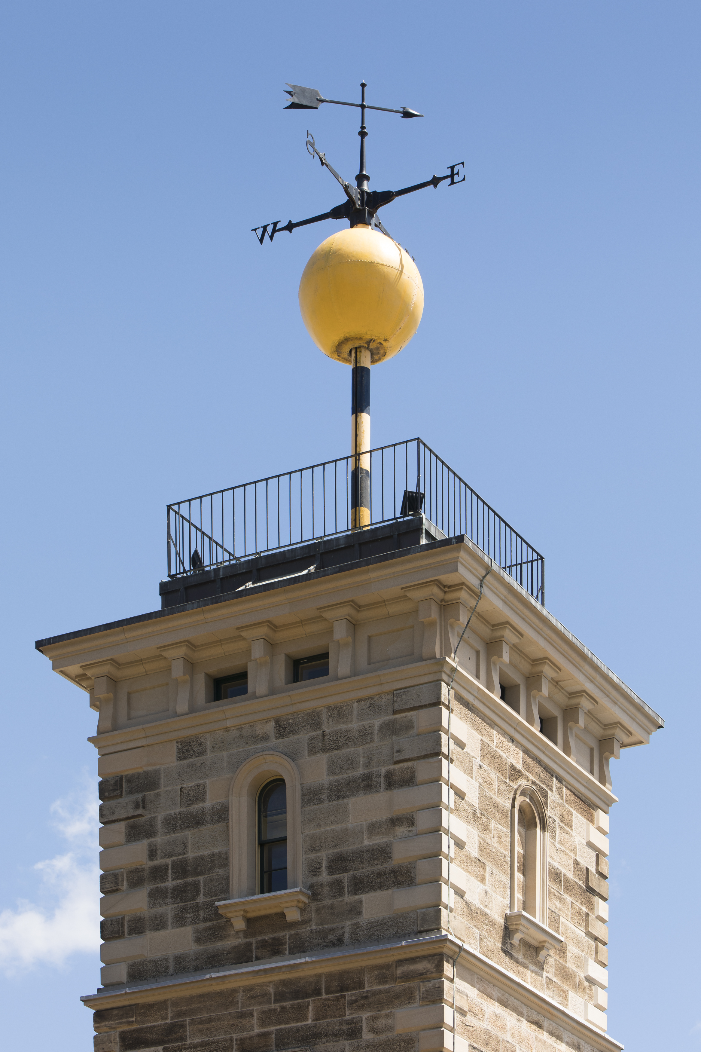 A large yellow metal call sitting on top of a sandstone tower with a weather vane above it.