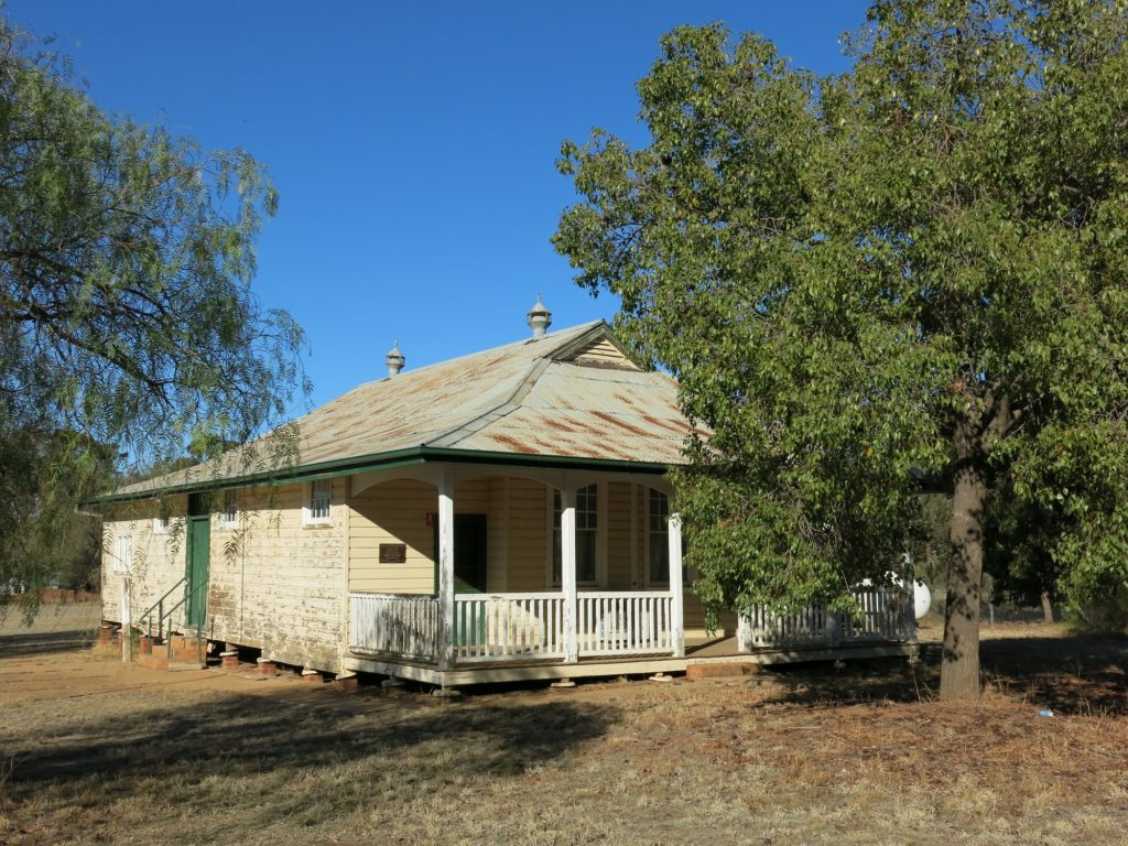 Photograph of a very small country school built of weatherboards with a verandah at the front and concrete area at the side for assemblies.