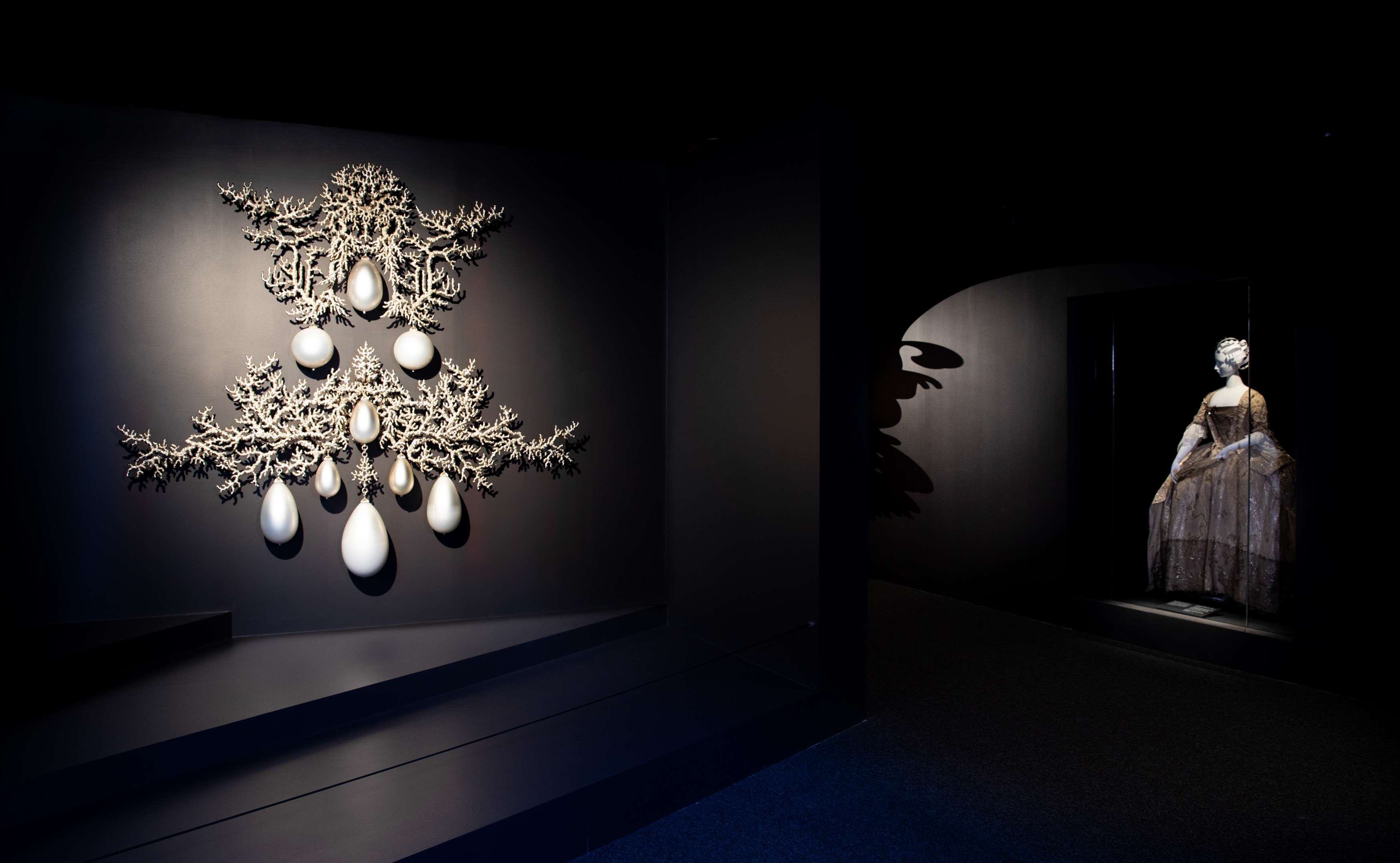 A symmetrical 2-piece wall artwork in the form of a huge pendant earring inspired by a baroque jewellery piece. It is made from a silvery cast-bronze structure which resembles flattened coral branches on which hang tear-shaped pearls made from hand-blown white glass with a mirror finish.