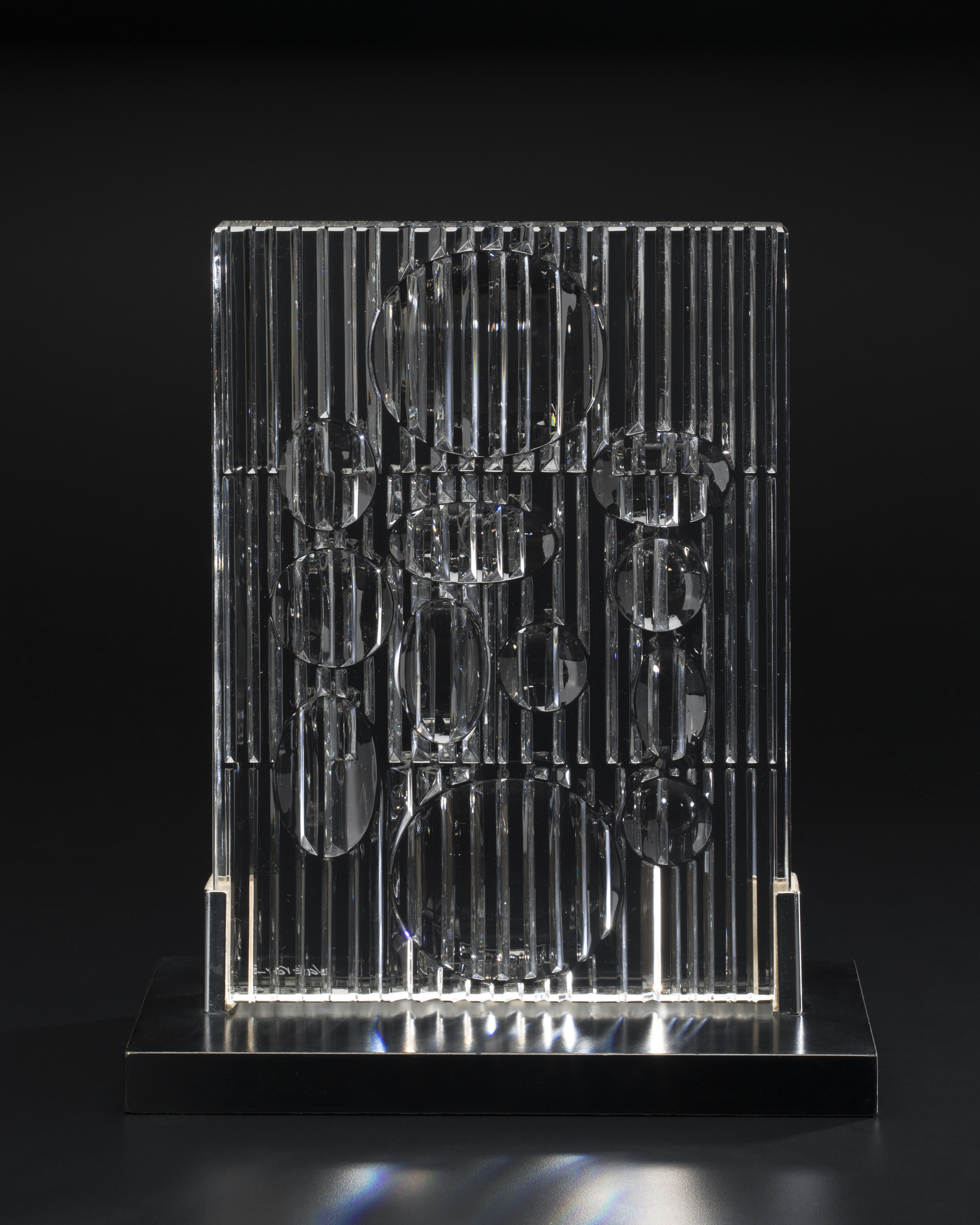 Standing rectangular panel in clear and brilliantly cut crystal, vertically reeded with round depressions which act as lenses to magnify the reeding and produce a rainbow-coloured effect on the crystal.