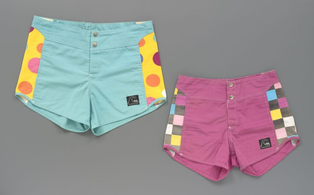 Two pairs of men's board shorts in green and pink with inserts on the sides consisting of multi-coloured polka dots or squares. There are two press-stud fastening and a Velcro fly at the centre front. A black brand label is stitched to the front left leg displaying a logo and the text 'Quiksilver' in silver thread.