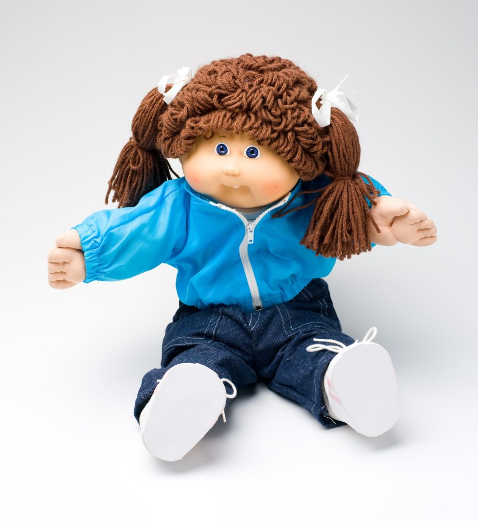 The Cabbage Patch doll has long brown hair tied into pigtails on either side of her head. The doll is dressed a light blue zip-up windcheater and dark blue denim jeans with white shoes. She has her arms out and is in a seated position.