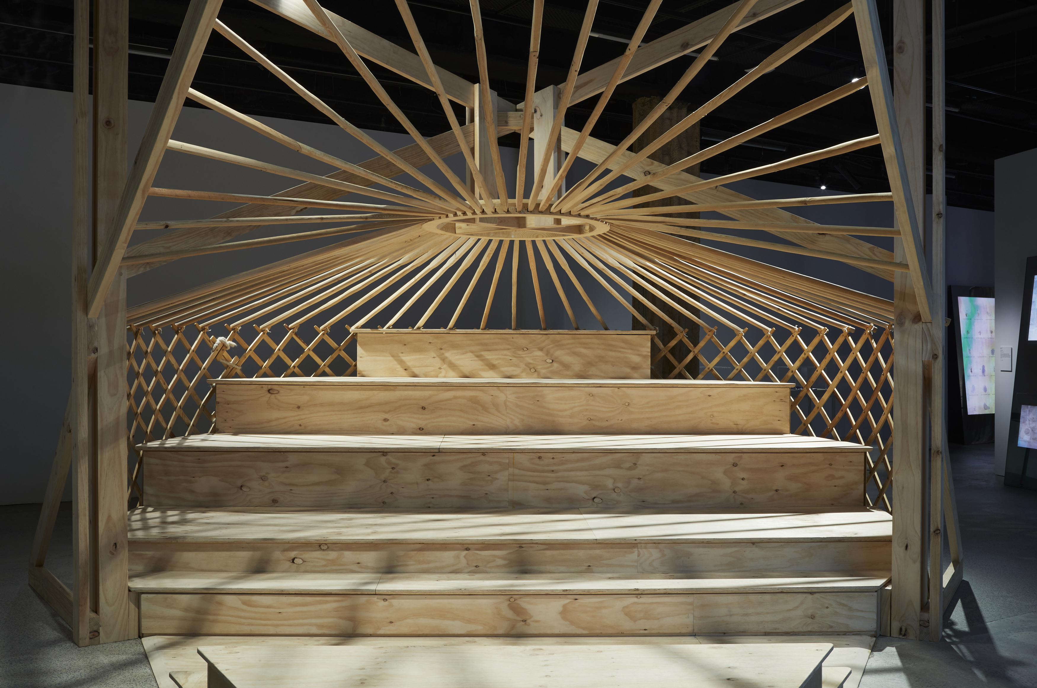 A five tiered wooden seating area with a latticed wooden framework behind and a central heating exhaust at the apex from which wooden beams connect to the latticed walls.
