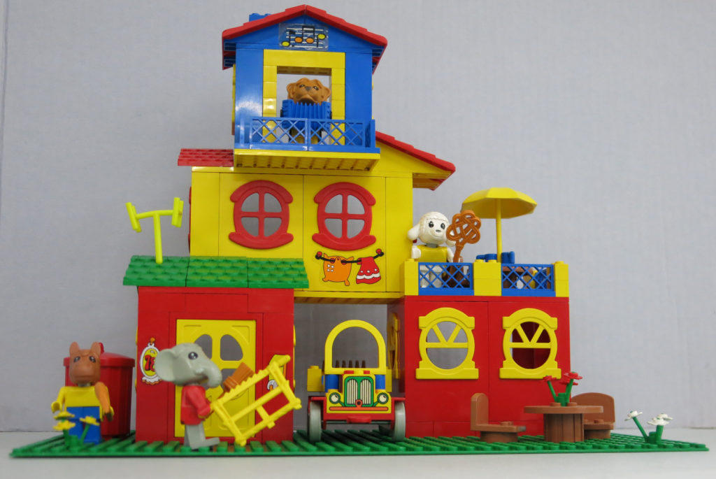 Fabuland Set No. 3678 Lionel's Lodge (Mayor's House or The Fabuland House), originally 135 (or 122 pieces?), including four Fabuland figures, Lionel Lion, the Mayor of Fabuland, Harry Horse, Lucy Lamb, and Edward Elephant. It features Lionel's three-storey house, Lucy Lamb with a carpet beater on the upstairs outdoor terrace, a car, a rubbish bin, saw, rake and paint brush.