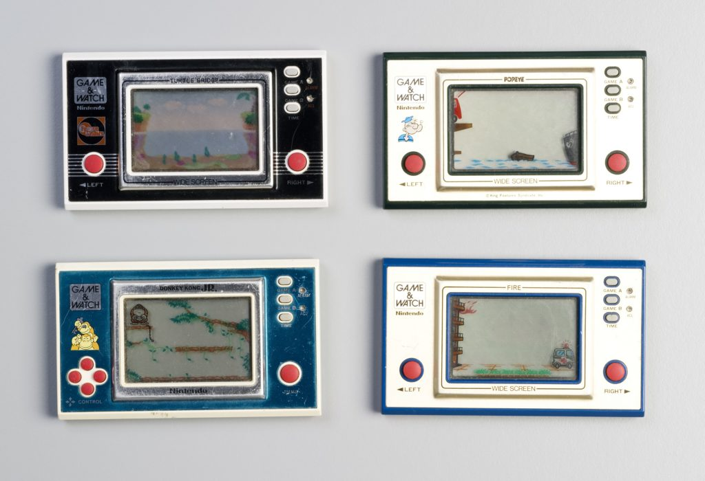 Four Nintendo Game and Watch electronic games. Each consists of a rectangular console with plastic casing and metallic front and an LCD display screen with permanent graphics incorporated. The LCD characters move through this display. The control buttons are red and there is a battery casing at the back. Decorative transfers. No packaging. The console is designed to be held comfortably in both hands and operated with the game controls under the thumbs.