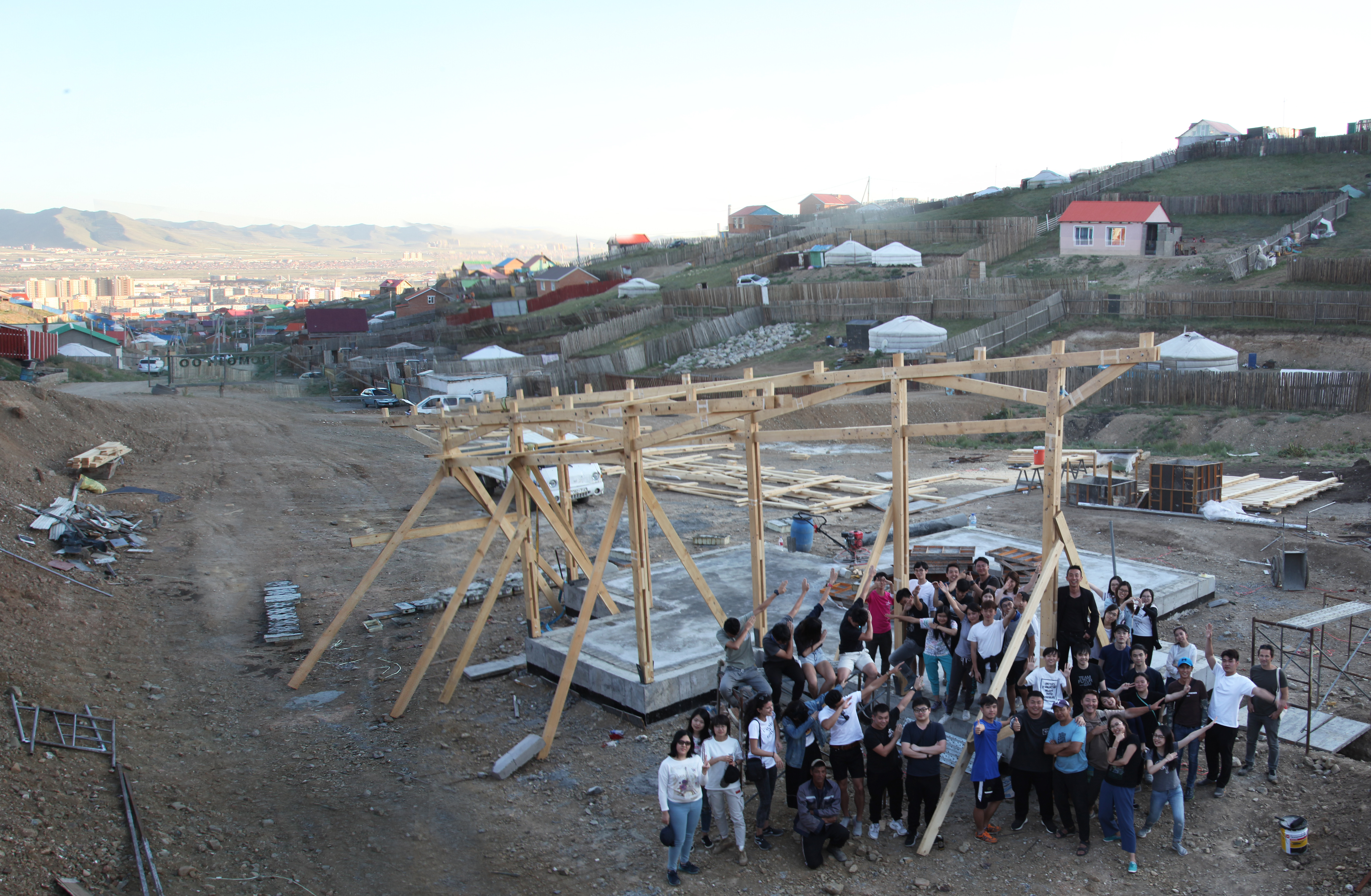 Students amassed in a construction site next to a partially constructed wooden framework. Individual ger plots can be seen on the hills in the distance.