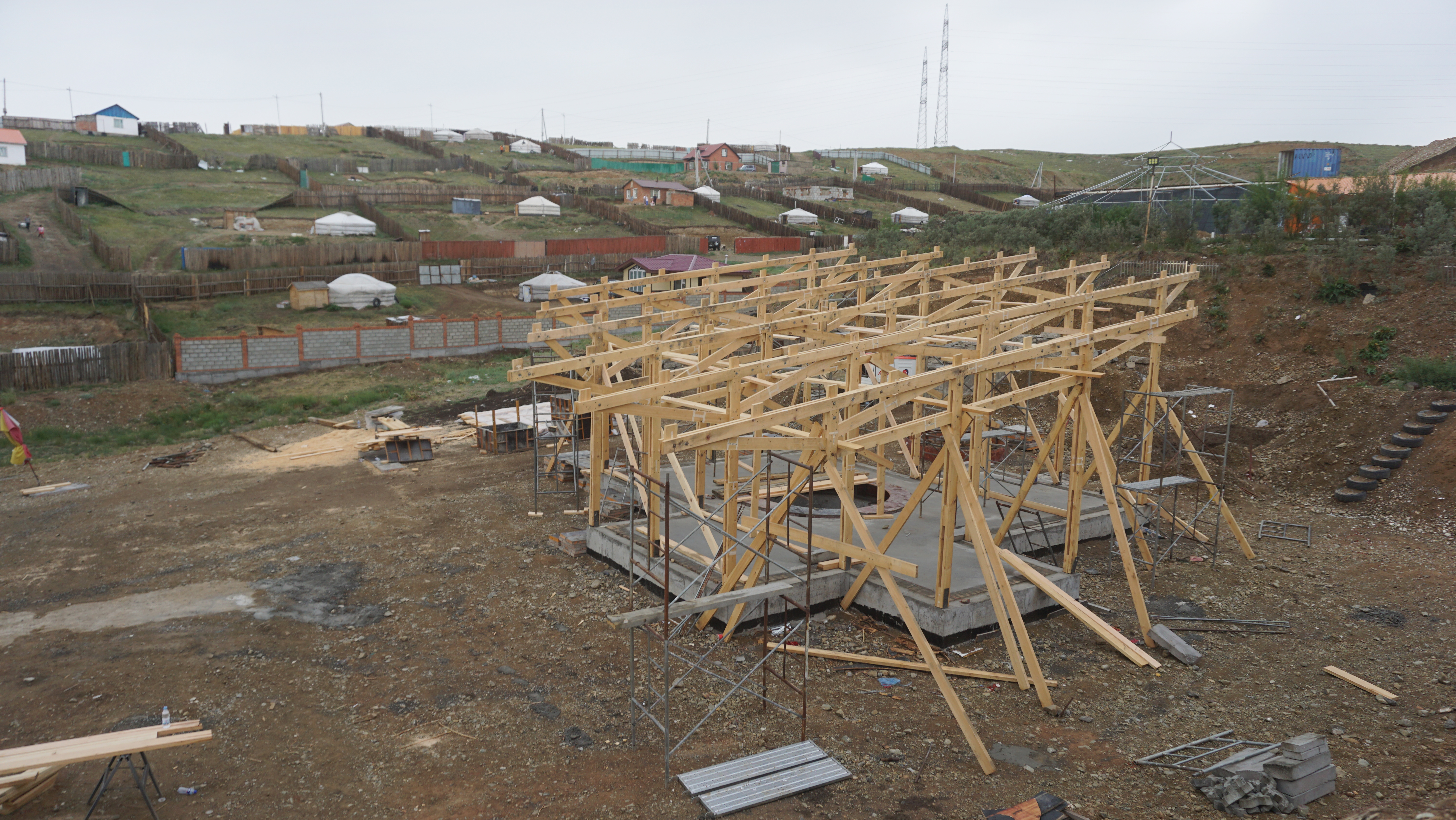 Poured concrete base with a laticced wooden framework roof mid-construction. Individual ger plots can be seen on the hills in the distance.