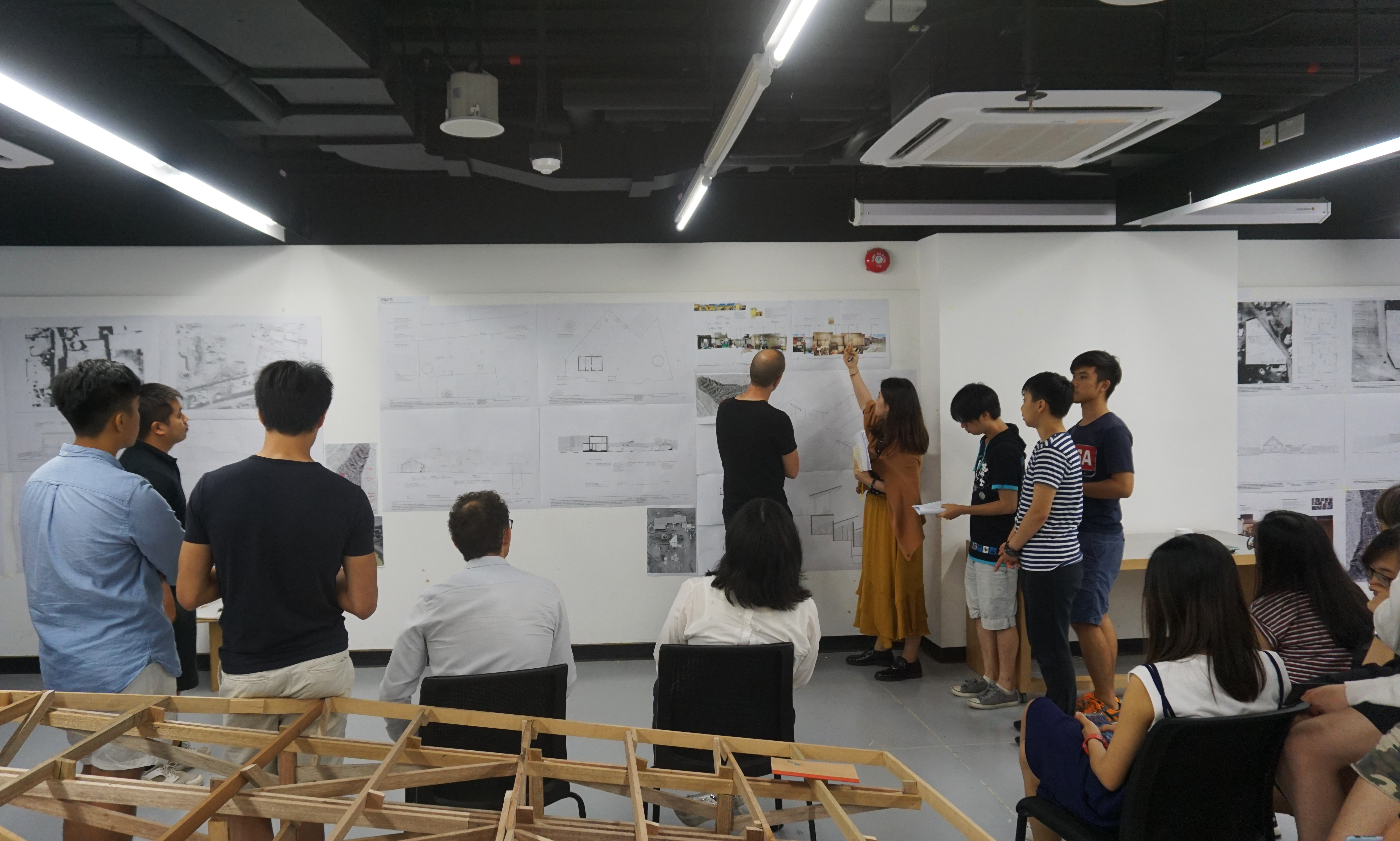 Students gathered together looking at architectural plans and related documents posted on the far wall.