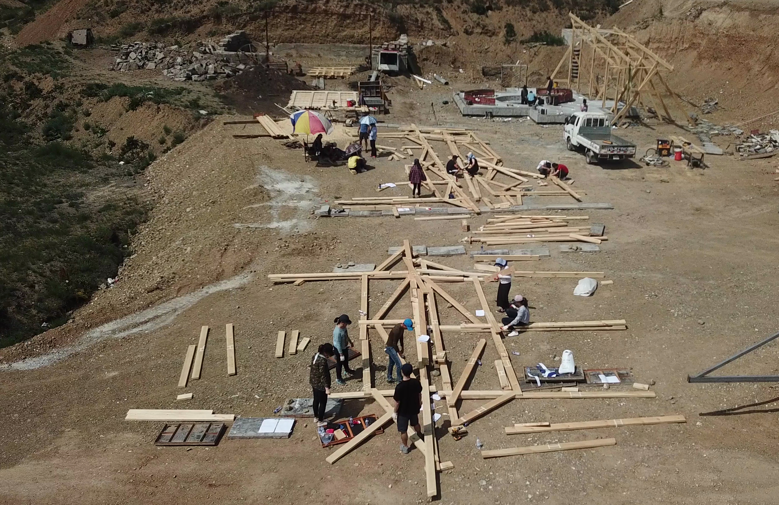 Construction site with wooden beams laid out on a dirt plain. People gathered around discussing the project.