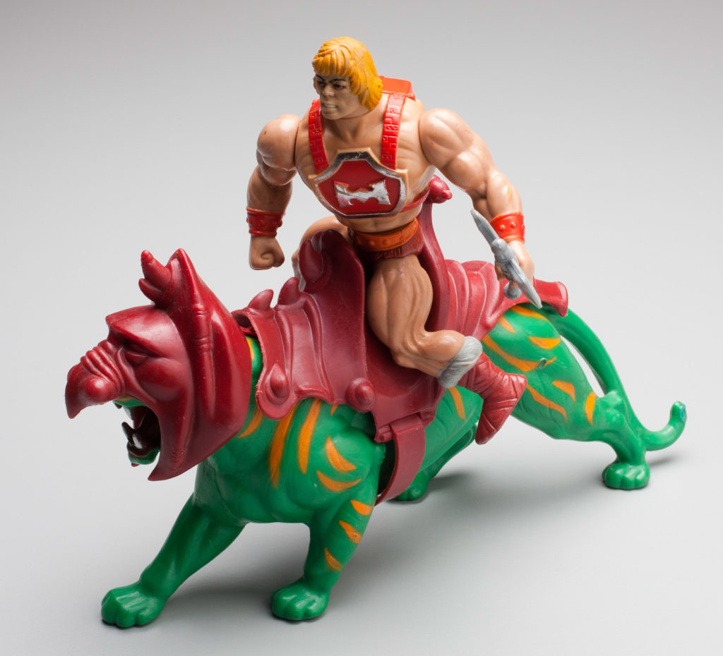 The moulded He-Man figure has a muscular body, blonde hair and wears a red chest plate with the letter 'H' strapped to his body. He wears red briefs, orange belt, orange wrist bands and long grey and red boots. He carries a grey double-edged broad axe in one hand and has a yellow sword and silver shield. The moulded green plastic Battle Cat figure features orange stripes and is modelled in a stalking position, mouth open and teeth bared in an aggressive manner. His head is covered with a red armoured helmet and on his back is a large red saddle.