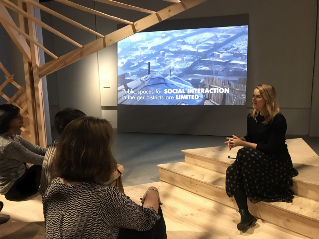 Woman sitting on wooden steps giving a talk to a group of people with presentation slides on the wall behind.