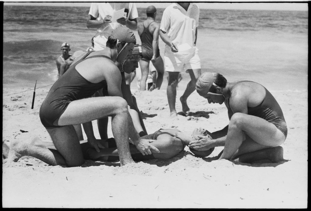 Black and white photograph showing three lifesavers wearing full strapped costumes and caps on the water's edge kneeling over a man on whom they are demonstrating resuscitation.