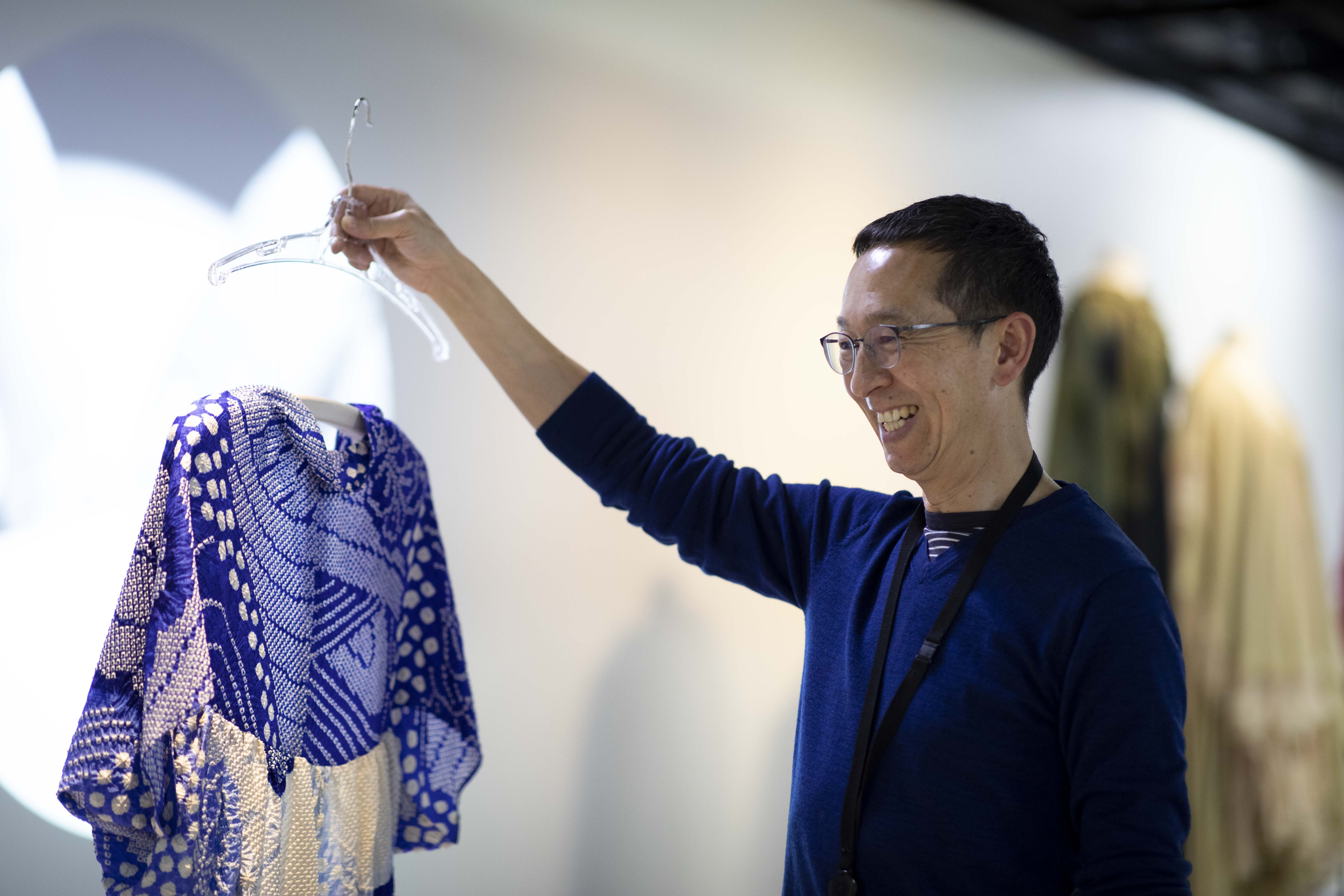 A man holding a coathanger from which drapes a blue and white patterned silk top. The man has a broad smile.