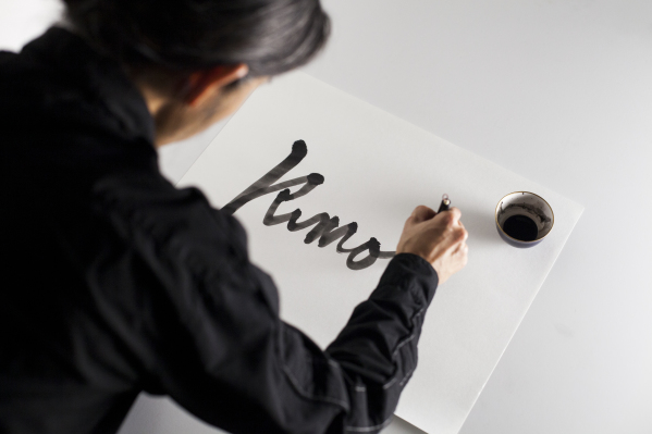Photograph taken over the shoulder of a man he paints the word 'Kimono' in calligraphy. The text is black on a white sheet of paper and there is an ink pot in the top right corner of the paper.