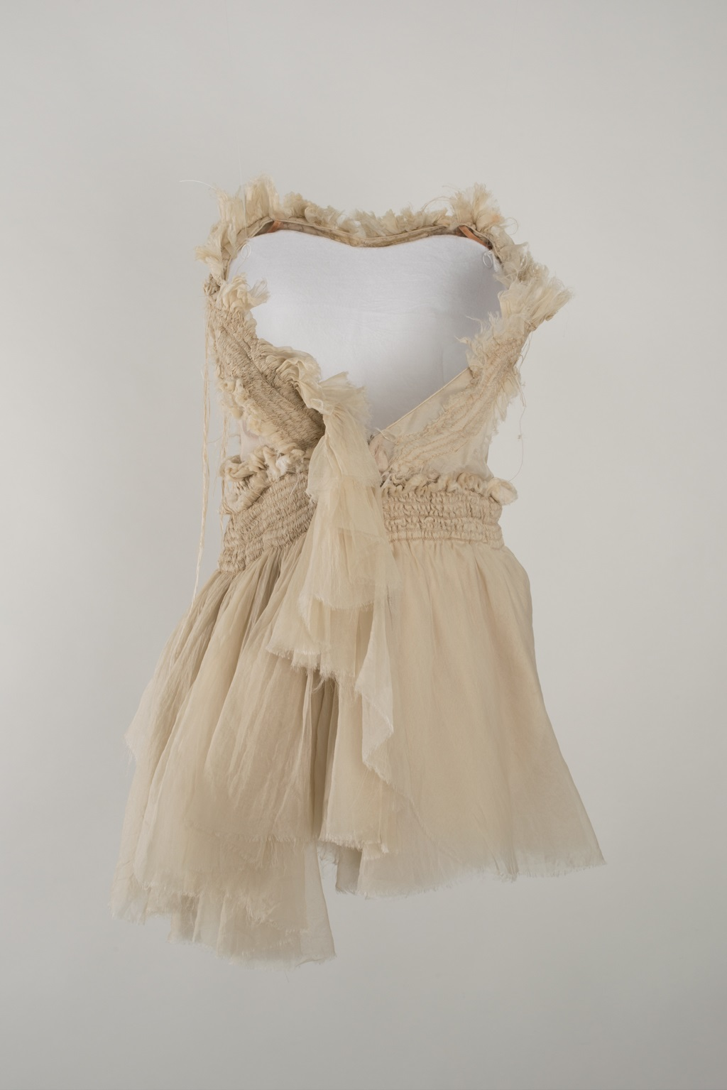 A dance costume designed by Akira Isogawa that is supported by one of the 'invisible' white moulded forms. The dress is made from off-white fabric, with a short skirt, wide v-neck and elasticated waist. The edges of the fabric are left deliberately frayed.