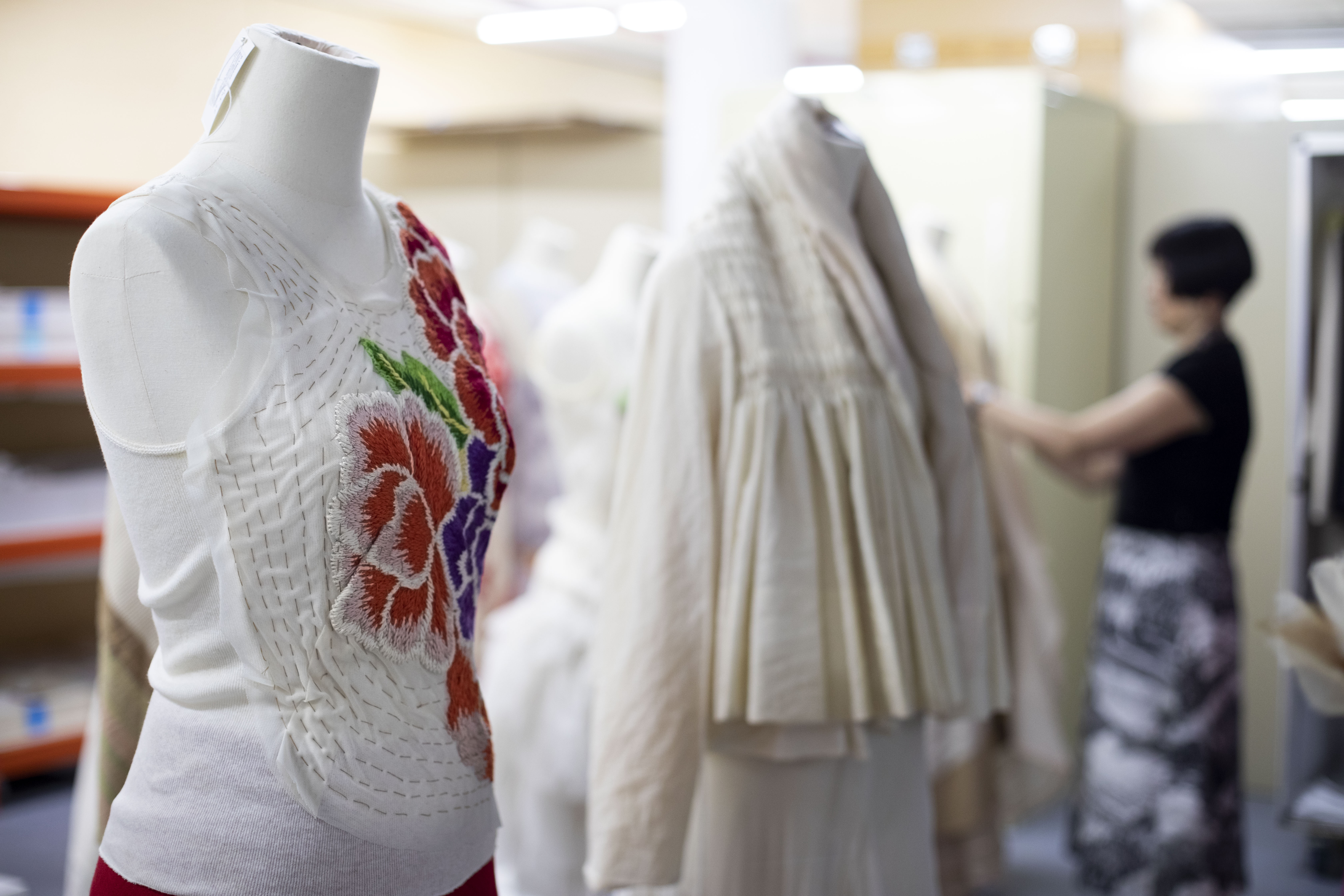 A white sleeveless top with floral applique pattern on a mannequin. In the background, out of focus, are a second dressed mannequin, and beyond that, a woman dressing a third mannequin.