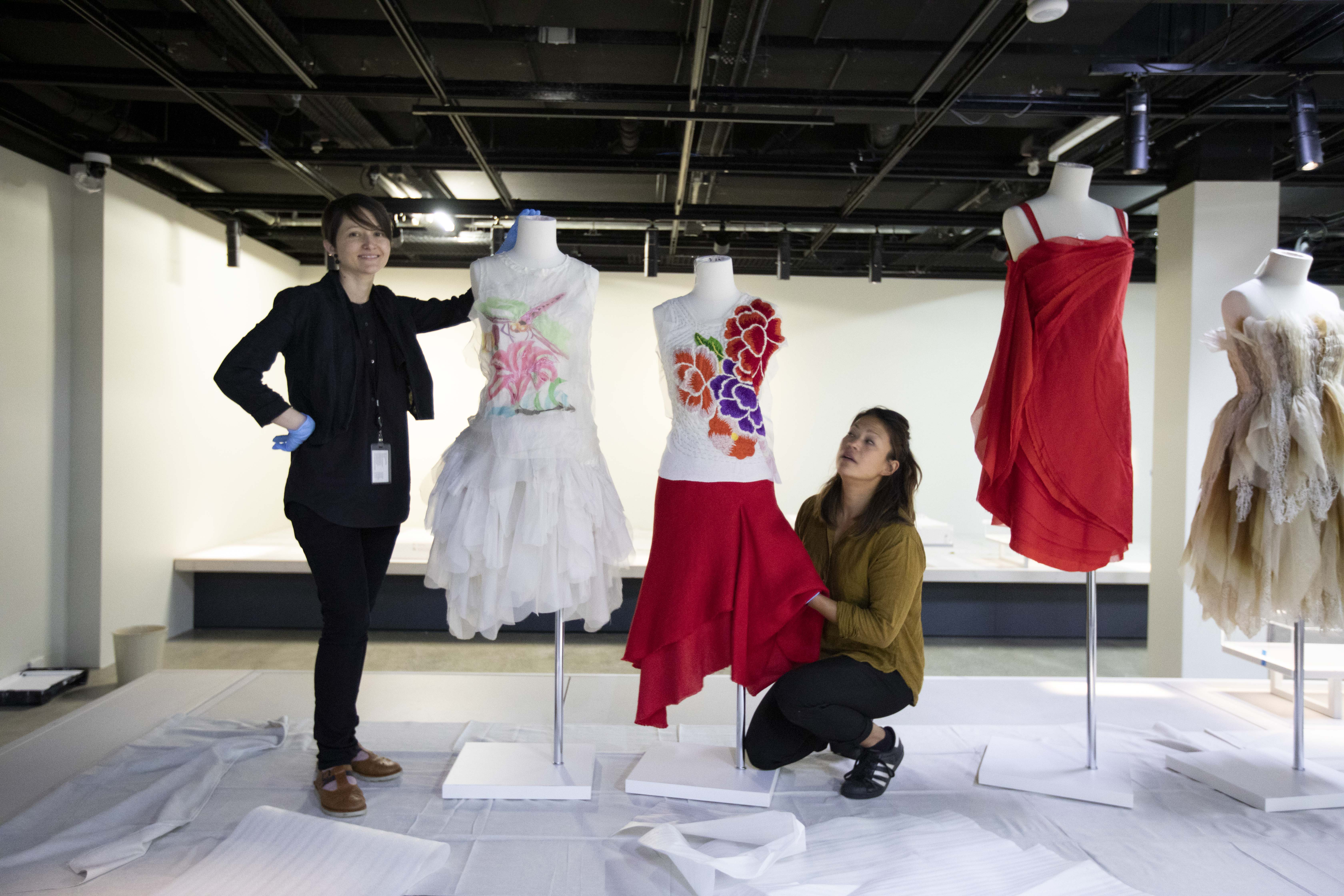 Two women in the process of placing the clothed dress forms into position on the display plinths.