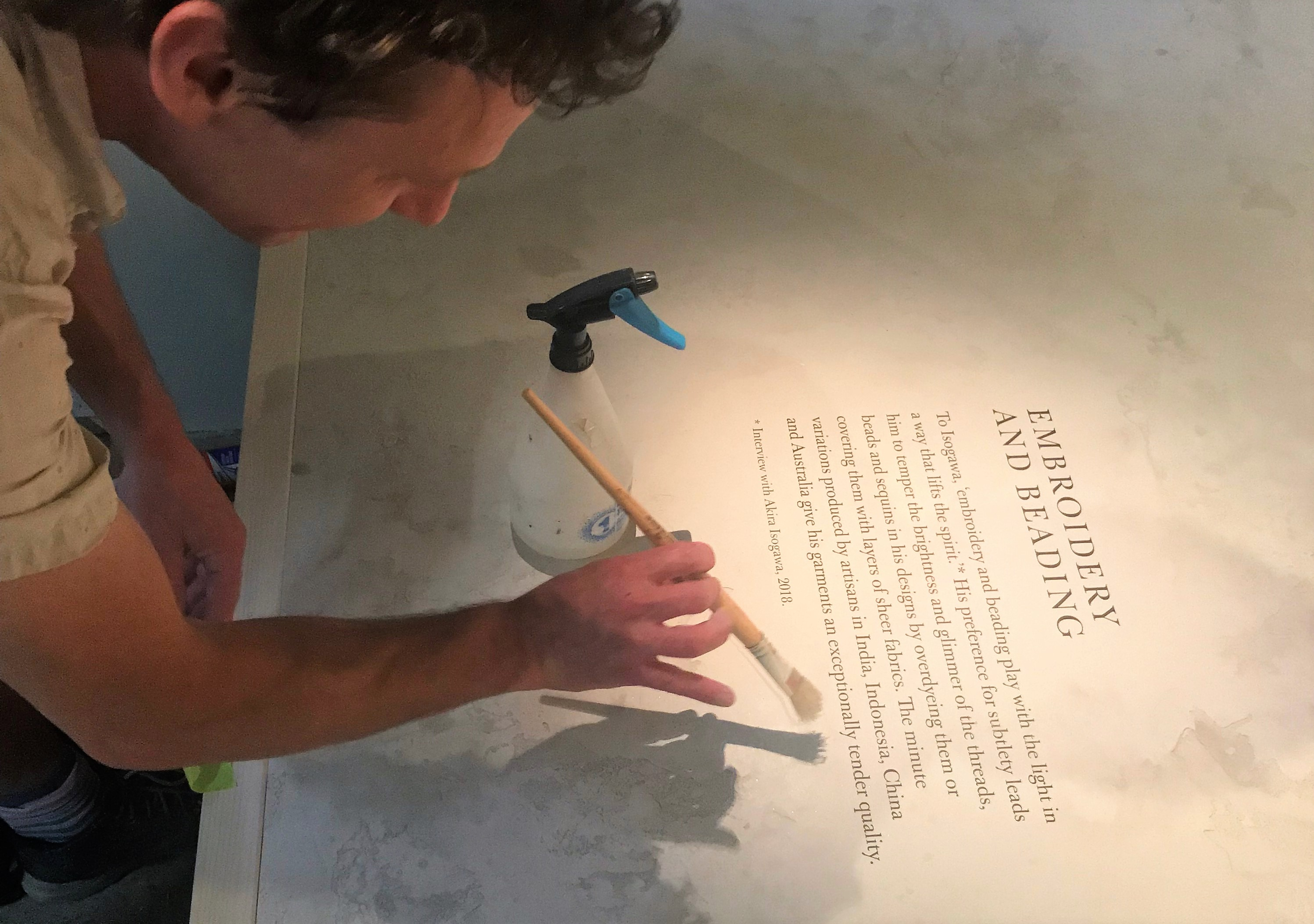 A man with a paintbrush poised over a plasterwork plinth. Written on the plinth is exhibition text with the heading 'embroidering and beading'. There is a spray bottle next to the man's hand.