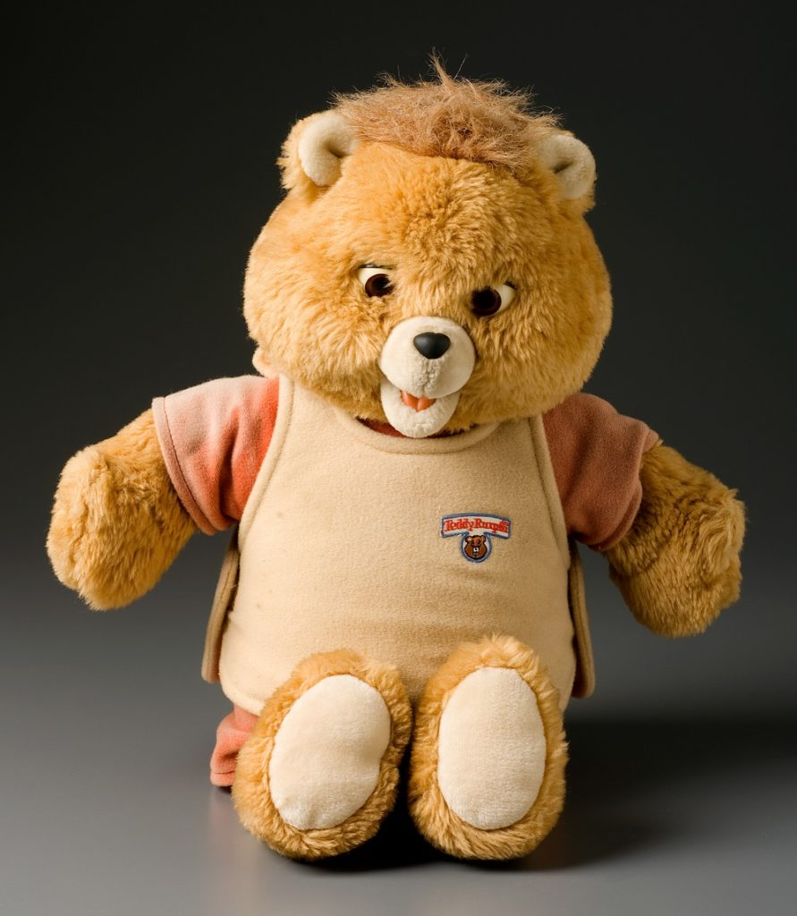 Animatronic toy teddy bear with plush fur body, large head, small ears and moveable mouth. The bear is light brown in colour and wears a short sleeved orange top beneath a tan coloured tunic. The tunic has an embroidered logo with the bear's name 'Teddy Ruxpin'. The body of the bear contains a cassette tape player which can be accessed by lifting the tunic. The inserted audio cassettes synchronise the talking apparatus which control the bear's mouth with the story heard on the tape.