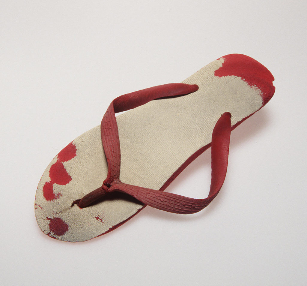 A single worn rubber thong from a pair with red soles and straps and white upper soles. The straps are moulded with musical notation motifs. The thong is so well worn to the point that the imprint of the heel and individual toes are worn into the red rubber.