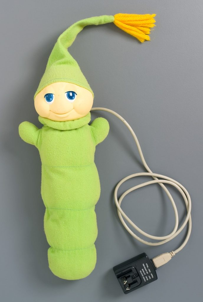 The Glo Worm is a soft plush toy in a bright green colour. The face is plastic and the body, arms and nightcap are green fabric. The nightcap has an orange tassel. Inside the body is a child-proof battery box and wire which activates the light which makes the face glow. When the body is pressed the light is turned on.