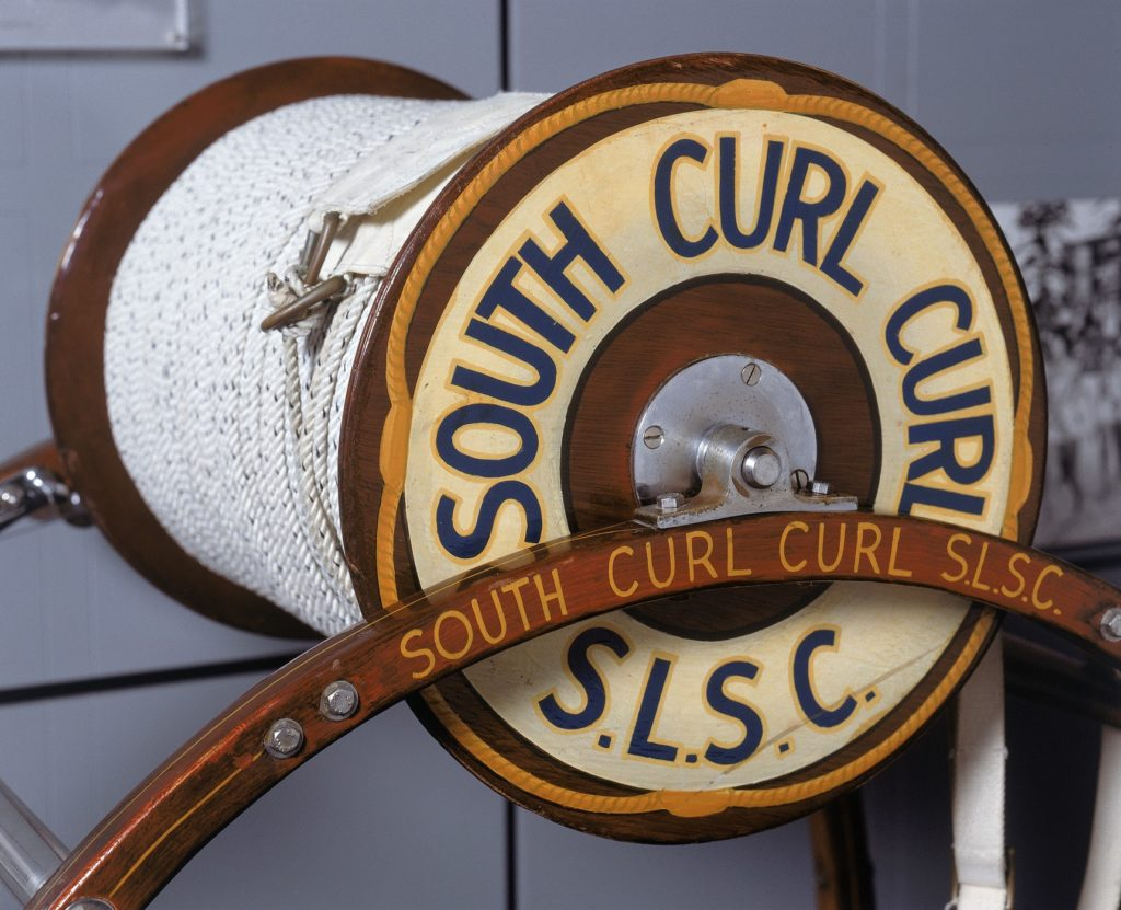The reel comprises a large, polished wooden cylinder with cotton rope wound around it. The cylinder is set in a frame stand which could be carried to the water's edge. The name of the surf club is painted on the sides of the cylinder.