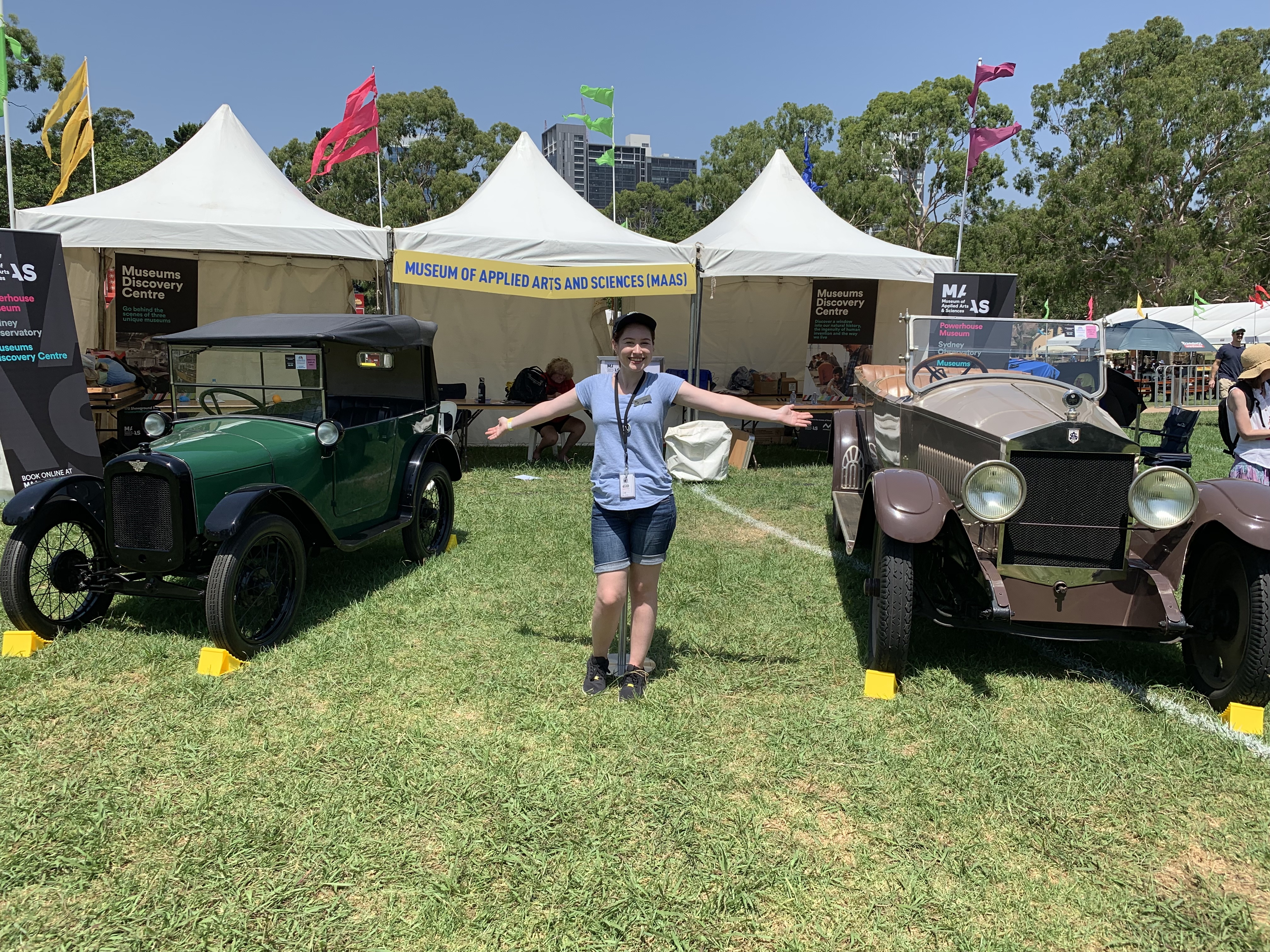 Small pale woman in a blue t-shirt, jean shorts and black cap stands on grass between two classic cars with her arms outstretched. Car on the left is green and black and the other on the right is light and dark brown. Behind her is a white fabric marquee with three roofed points and multicoloured flags blowing in the breeze.