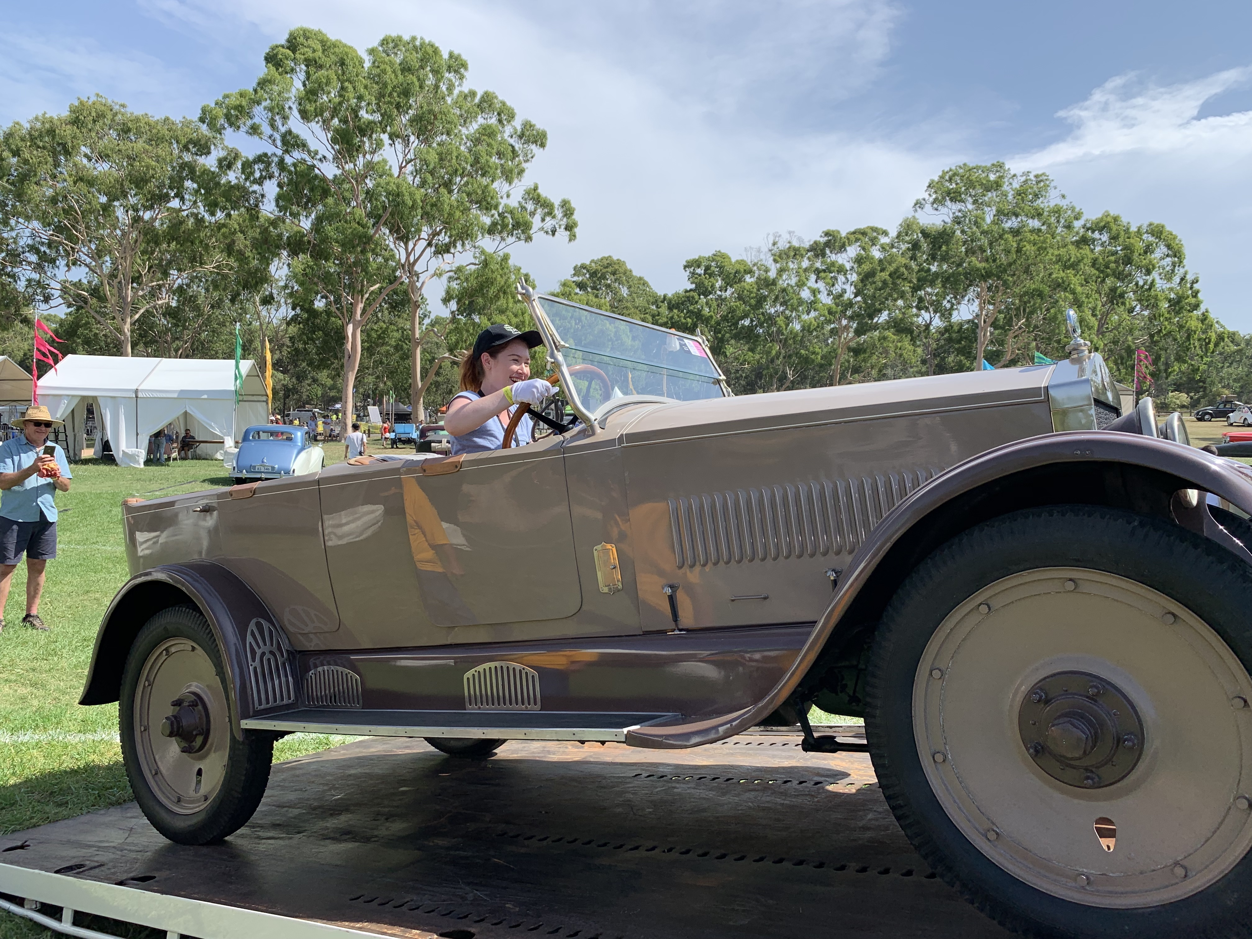 Pale woman in a light blue t-shirt and a black cap wearing white cotton gloves is steering a dark and light brown classic car onto a trailer of a low loader. A man wearing a blue button-down shirt, blue shorts and a straw hat is in the background to the left side taking photos on a phone.