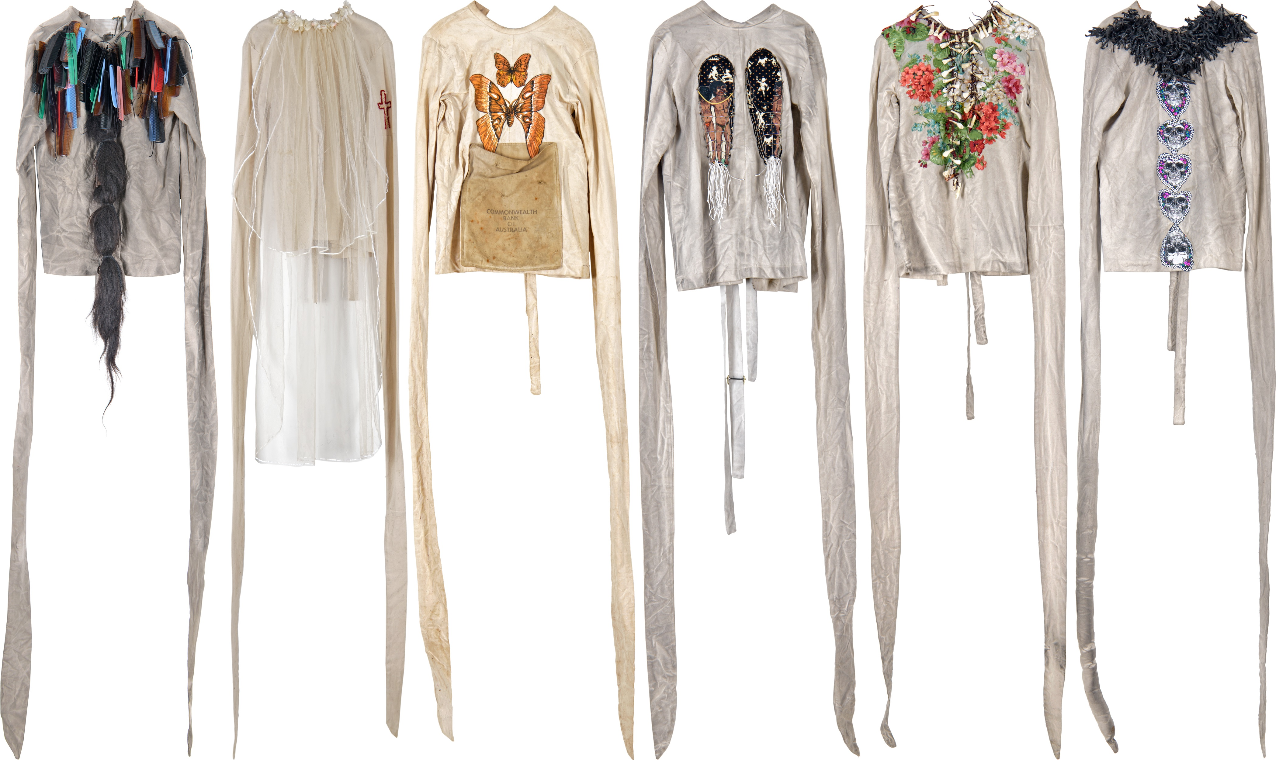 six straight jackets with images and objects attached, from left to right combs and hair, lace and embroidery, butterflies, images of people and dog muzzles, flowers and teeth, skulls and rubber