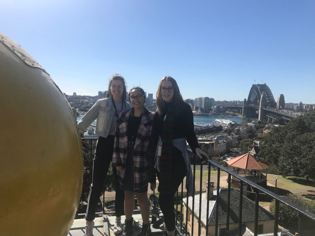 The museum interns stand beside a large yellow ball on a high tower. The Sydney Harbour Bridge is in the background.
