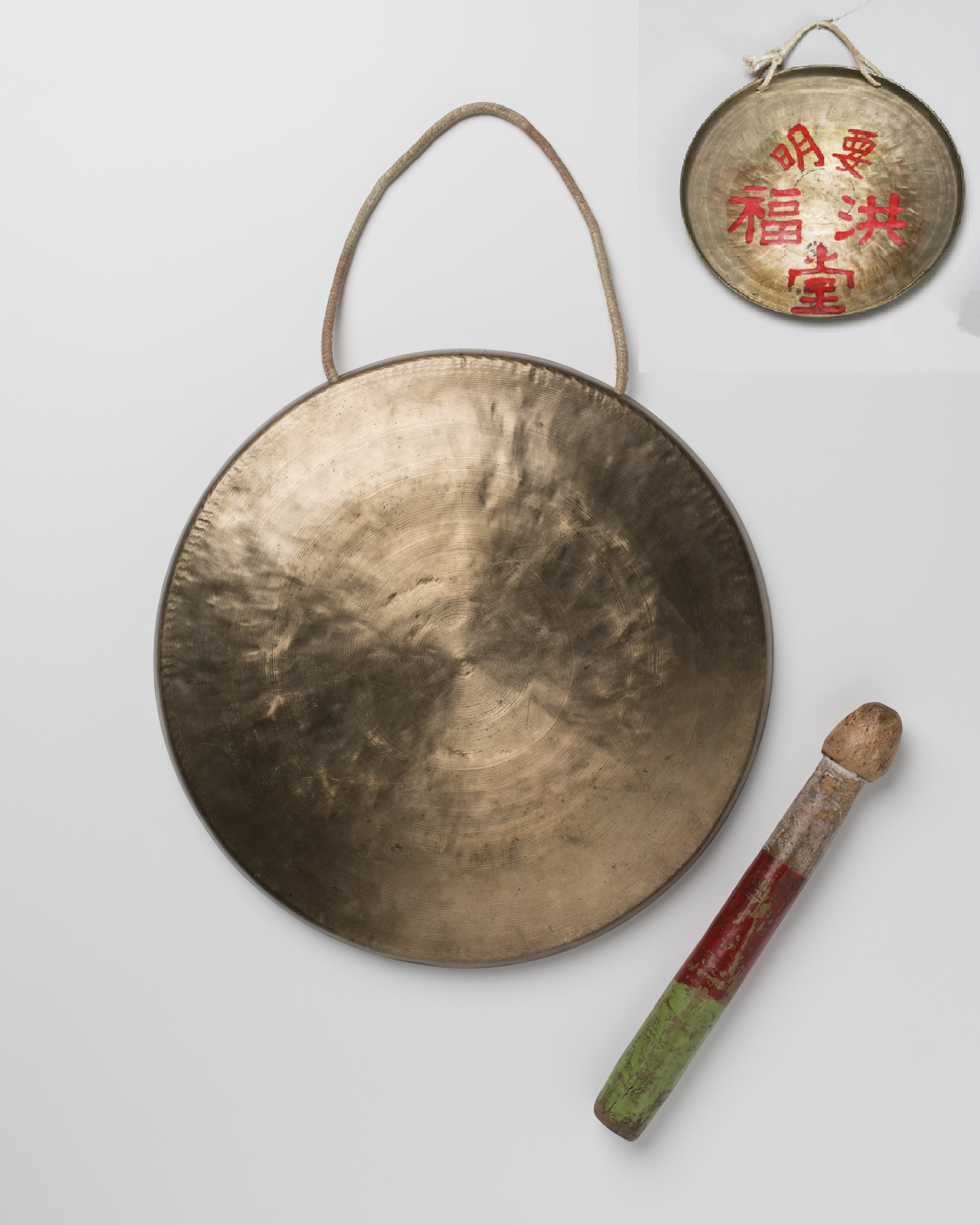 An image of a circular brass gong with cotton cord handle attached with its painted wooden beater to the side. A small image of the reverse of the gong with Chinese characters in red is in the top right corner of the image.