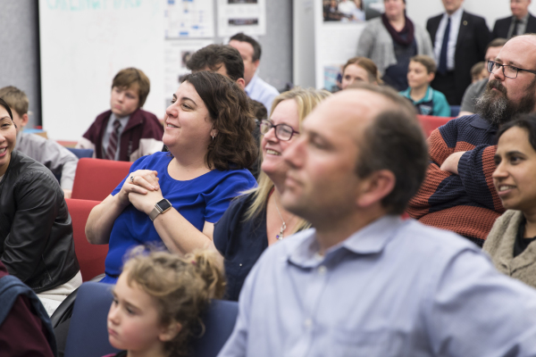 Audience of adults and children watches a presentation